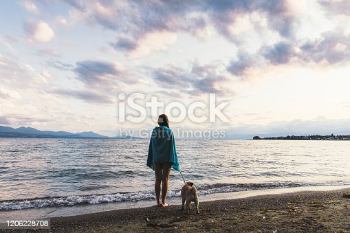 Young woman covered by blue towel and her small dog - pug breed resting after swimming in Geneva lake in Swiss Alps walking at the lakeshore during bright colorful summer sunset