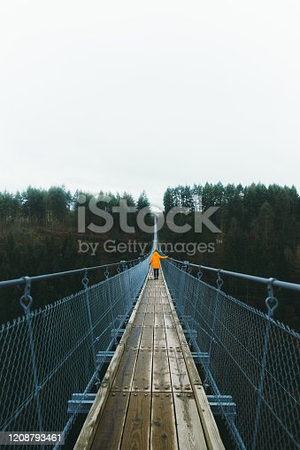 Young woman  in orange raincoat and her small cute dog - pug breed hiking on the big and beautiful suspension bridge in Germany