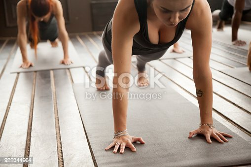 914755448istockphoto Woman and a group of sporty people in Plank pose 922344964