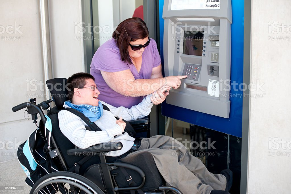 A woman and a handicapped man using an ATM royalty-free stock photo
