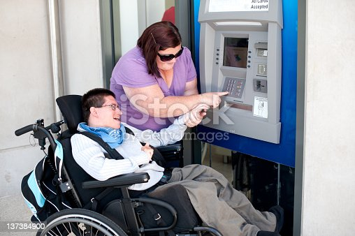 istock A woman and a handicapped man using an ATM 137384900