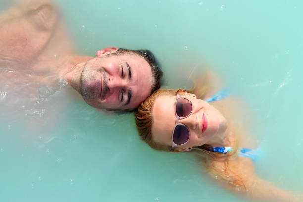 woman and a man in blue lagoon in iceland - hot spring stock photos and pictures