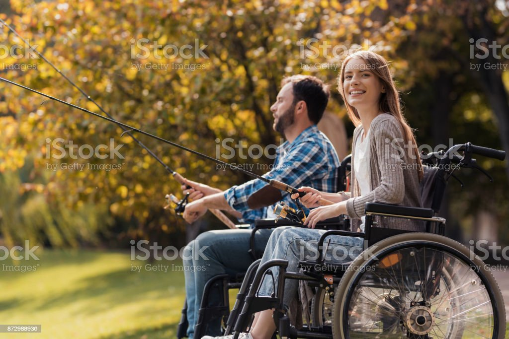 A woman and a man in wheelchairs are sitting on the lake shore. They have spinners in their hands and they are fishing. stock photo