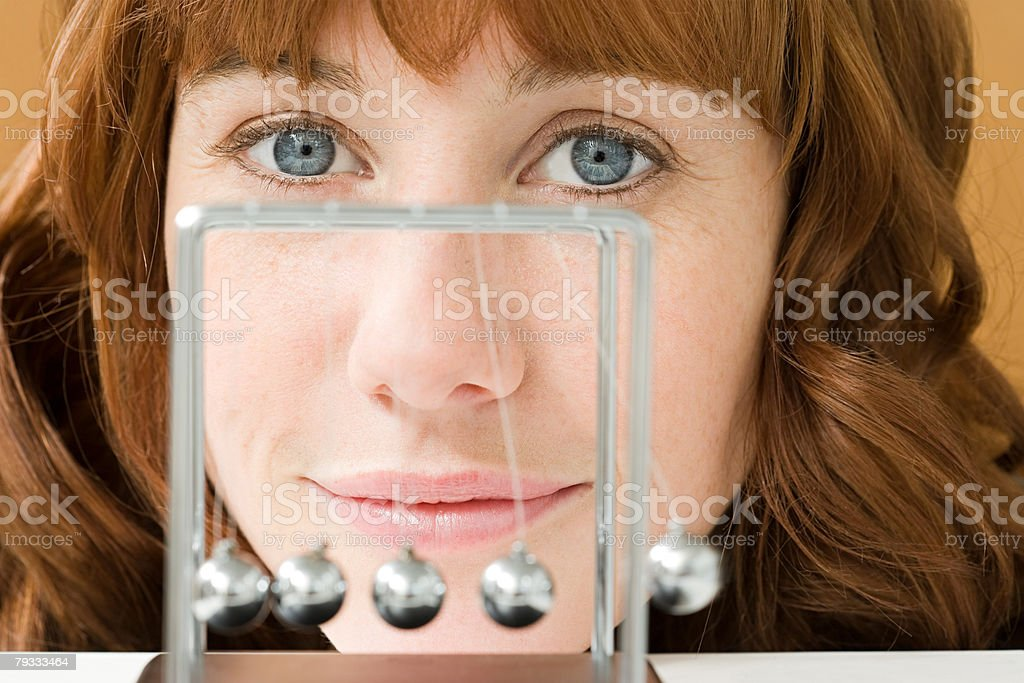 A woman and a newtons cradle 免版稅 stock photo