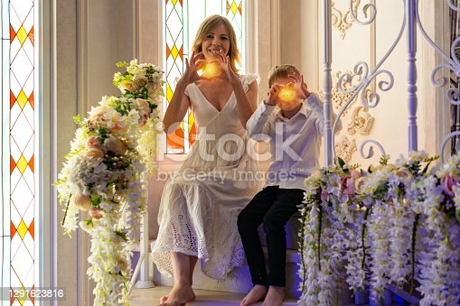 A woman and a young boy show a heart out of their hands. Love between mom and son.