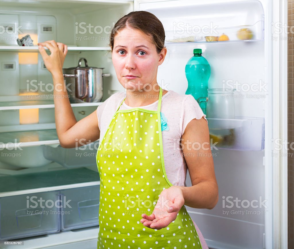 Woman and an empty fridge stock photo
