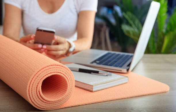 Woman and an exercise mat in an office background - foto stock