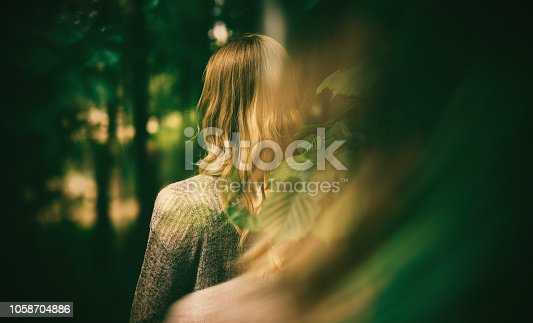 624717328istockphoto Woman and autumn forest. 1058704886