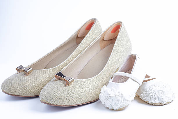 Mujer y zapatos de bebé sobre fondo blanco - foto de stock