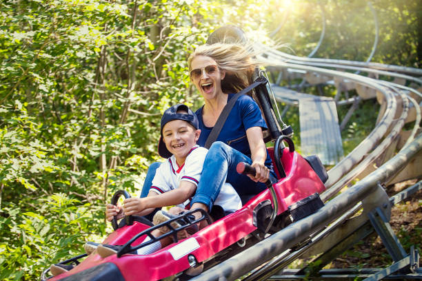 woman and boy enjoying a summer fun roller coaster ride - roller coaster stock pictures, royalty-free photos & images