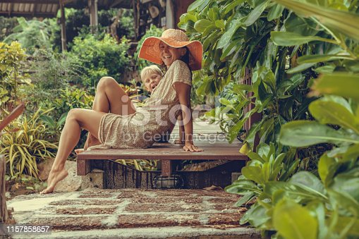Pretty Woman in boho dress and her son in the tropics