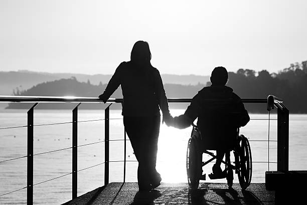 Woman and boy in wheelchair holding hands by the sea. stock photo