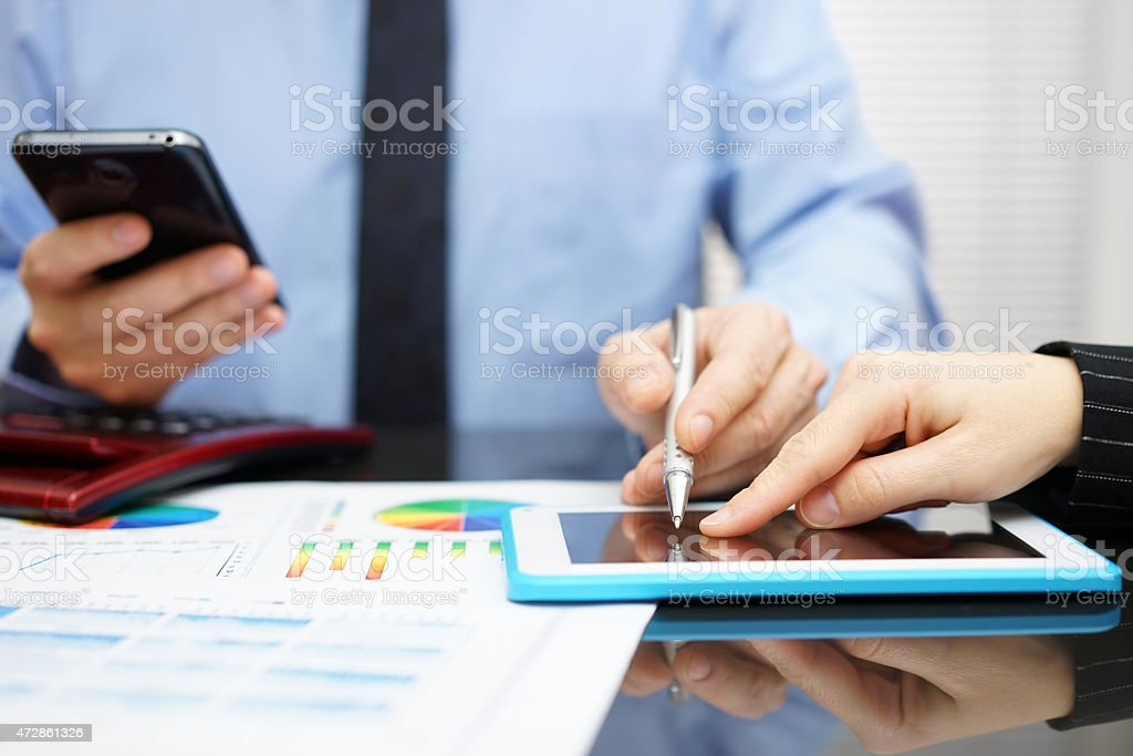 Woman and businessman with mobile phone reviewing report on tablet stock photo
