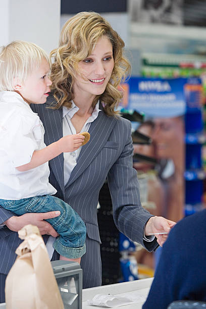 frau und kind beim check-out - kleinkind busy bags stock-fotos und bilder
