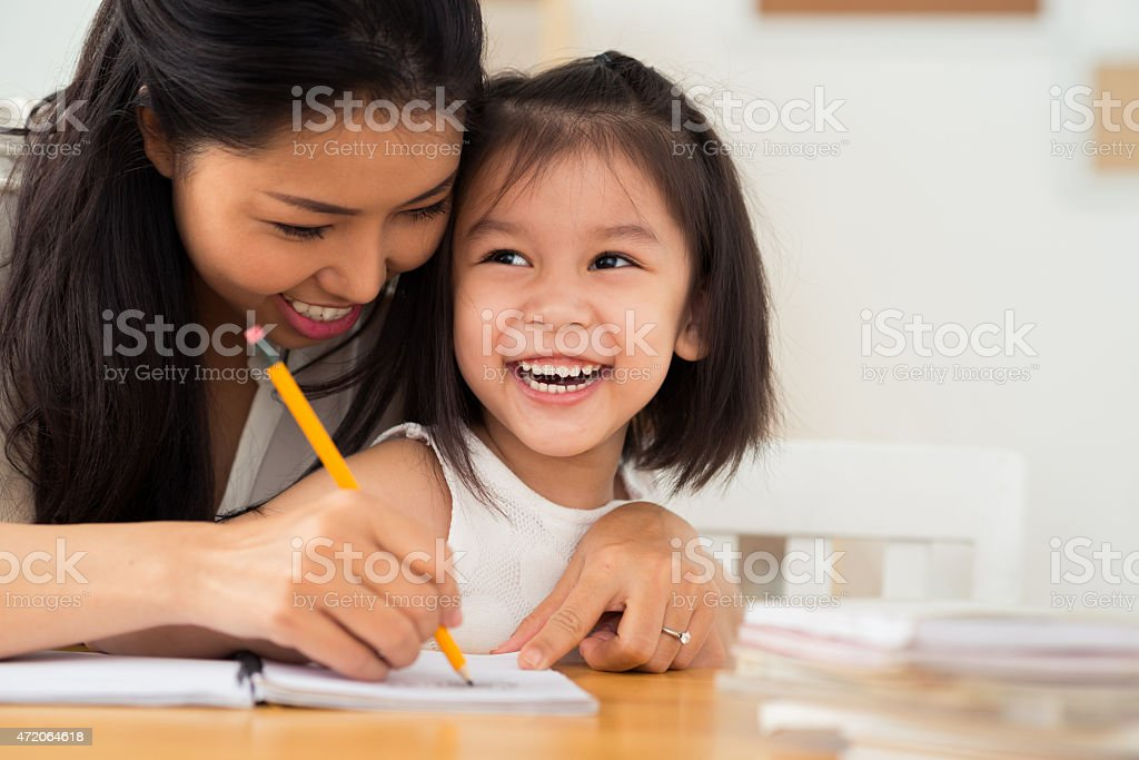 Woman and child drawing together with pencil and paper stock photo