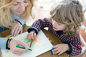 Woman and child drawing with crayons