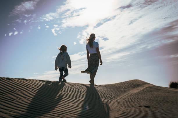 Mujer y niño en la playa caminando hacia el sol - foto de stock