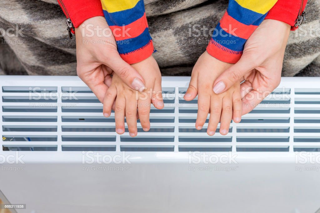 Woman and child warm up hands over electric heater. stock photo