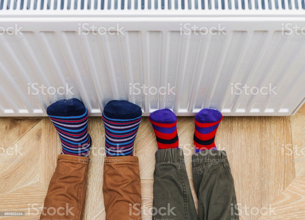 Woman and child wearing colorful pair of socks warming cold feet in front of heating radiator. Gas heater at home. Selective focus. stock photo