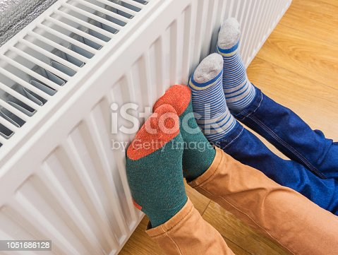 Woman and child wearing colorful pair of woolly socks warming cold feet in front of heating radiator in winter time. Electric or gas heater at home. Part of body, selective focus.
