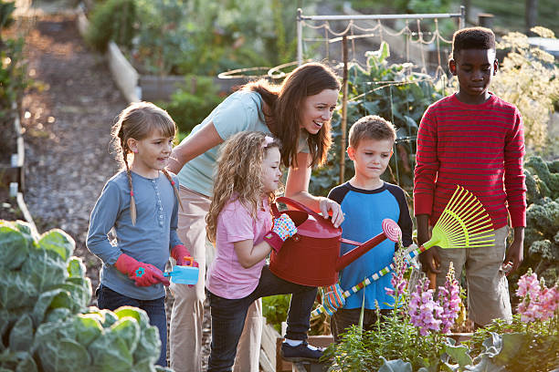 Woman and children at community garden Woman (30s) with group of children (5 to 10 years) at community garden. community garden stock pictures, royalty-free photos & images