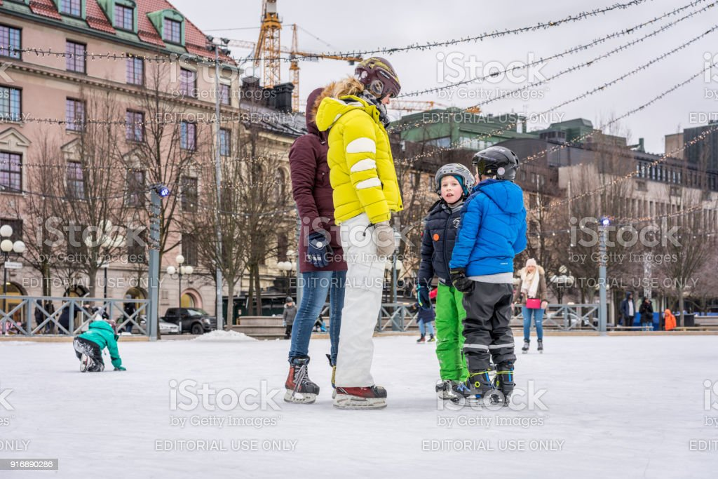 Woman and children ice skating in the city of Stockholm. stock photo