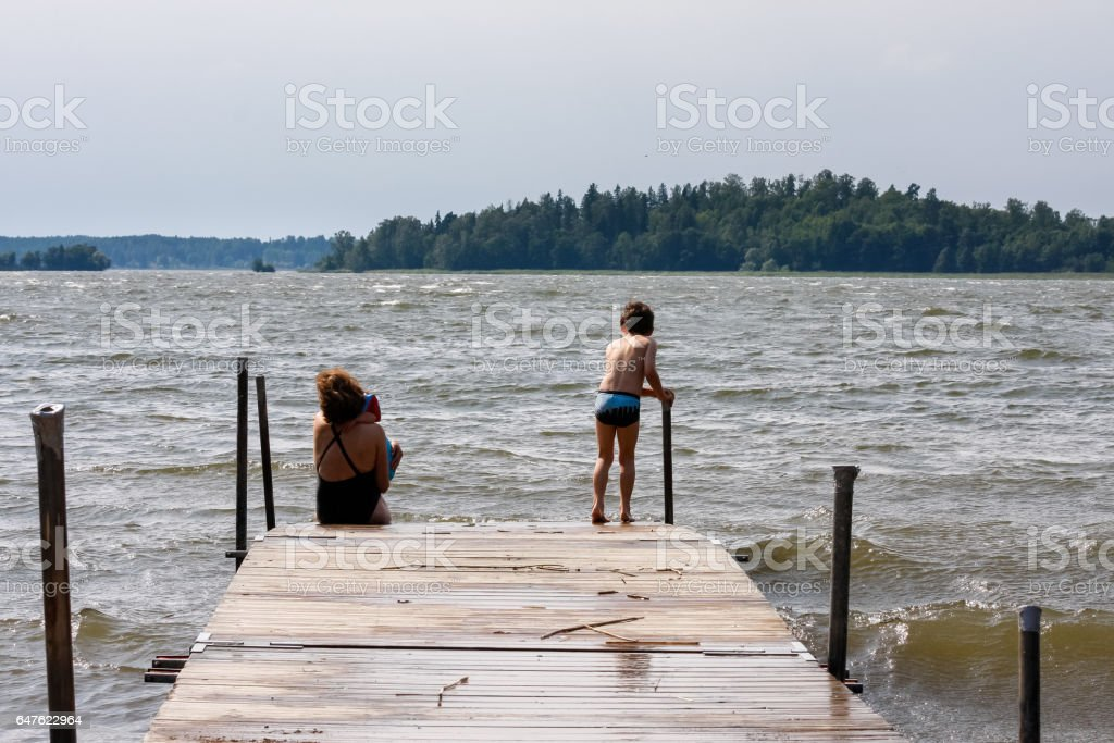 Woman and children in swimsuits at the end of a jetty with stormy waves. Family looking at restless sea. stock photo