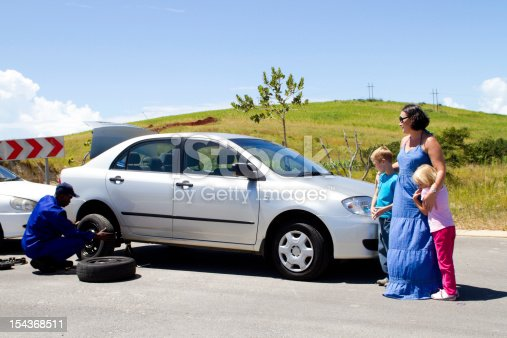 104275470istockphoto Woman and children watch as man changes their car tire 154368511