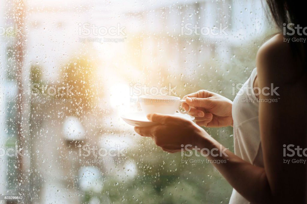 woman and coffee in hands looking through the glass window with a rain drops on city background stock photo