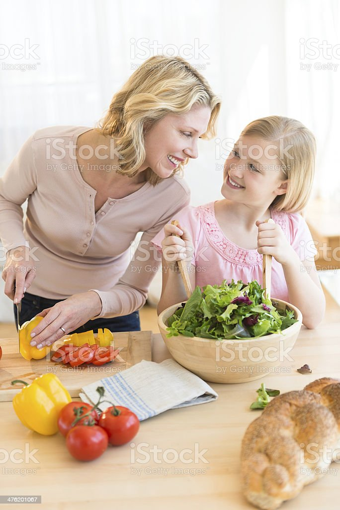 Woman And Daughter Looking At Each While Preparing Salad royalty-free stock photo