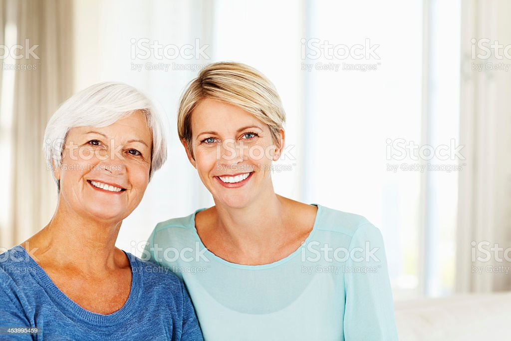 Woman And Daughter Smiling Together At Home Portrait of senior woman and daughter smiling together at home. Horizontal shot. 30-34 Years Stock Photo