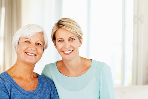 Woman And Daughter Smiling Together At Home Stock Photo - Download Image Now