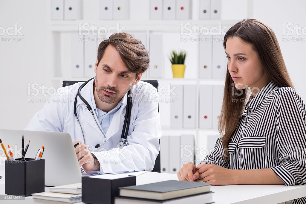 Woman and doctor look at screen photo libre de droits