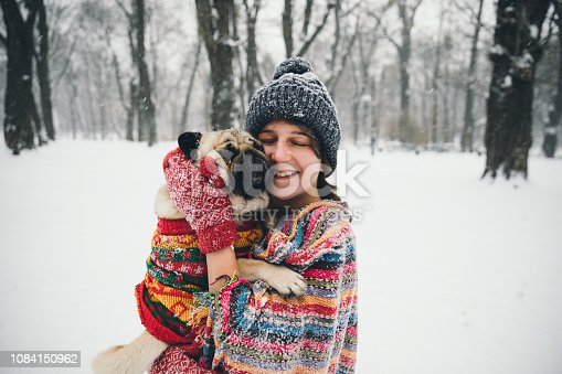 Woman in blanket and a small pug enjoying the snow day at the city park over Christmas holidays