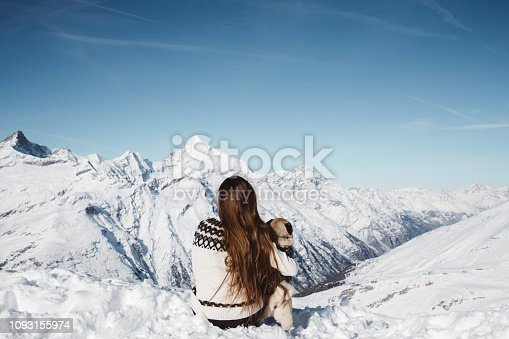 Woman and dog in wool sweaters enjoying the day at Gornergrat in Zermatt looking at Swiss mountain peaks