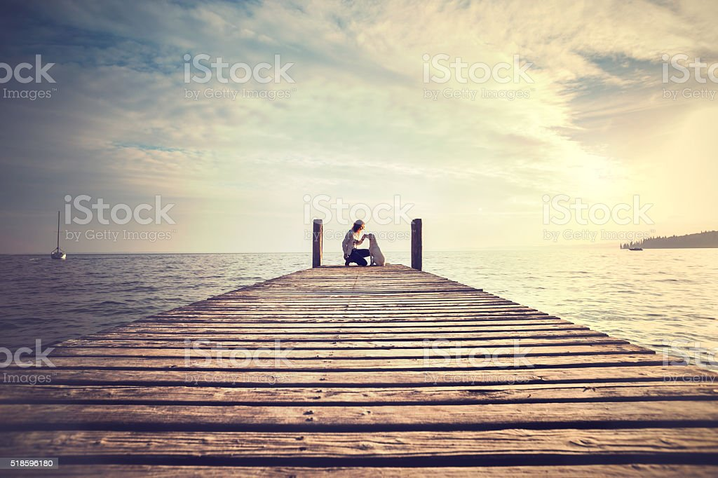 woman and dog from behind admire together the scenery stock photo