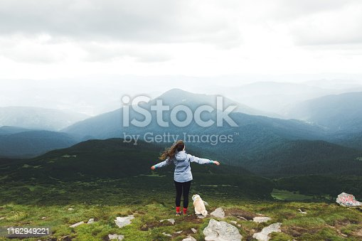 Young woman in blue jacket and her small fluffy pug having fun and feeling freedom and happiness finally hiked to the highest peak of Carpathian Mountains in Ukraine - Hoverla