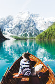 Young smiling woman in striped shirt and her small fluffy pug enjoying the bright summer sunny morning on the orange boat at turquoise mountain lake in South Tyrol - Italy