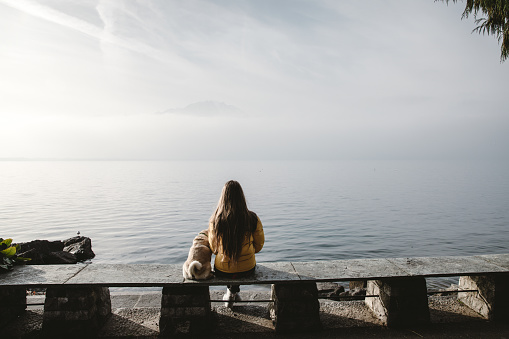 Woman and dog looking at foggy mountains and lake Geneva in Montreux