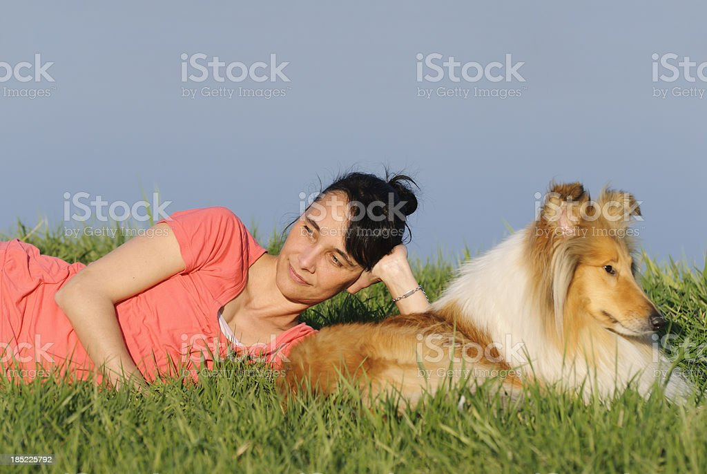Woman and dog lying in the grass stock photo