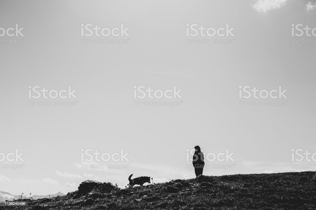 Woman and dog silhouettes standing on a cliff edge high up in the...