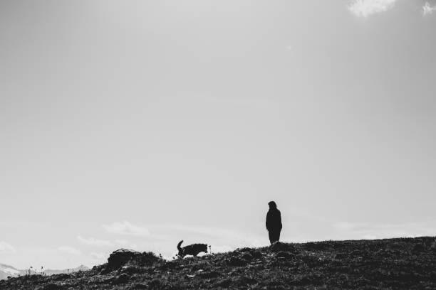Silhouetten von Frau und Hund an einer Klippe – Foto
