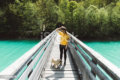 Young woman with long hair in yellow t-shirt and her small fluffy cute pug walking to the forest on the bridge above lake Plansee in tirol, Austria - bright summer day