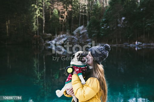 Woman and a small dog - pug enjoying the day at beautiful turquoise lake Blausee in Swiss Alps