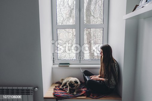 Woman with long hair sitting on window sill using laptop and sleeping pug, looking at snow from the window