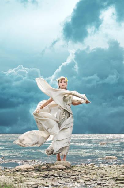 frau und frische meeresbrise - toga kostüm stock-fotos und bilder