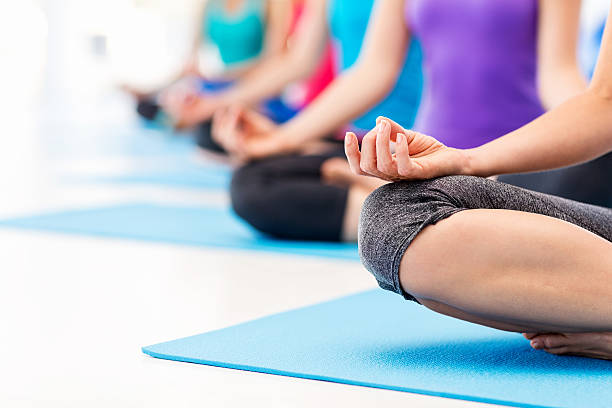 Woman And Friends Practicing Yoga In Health Club stock photo