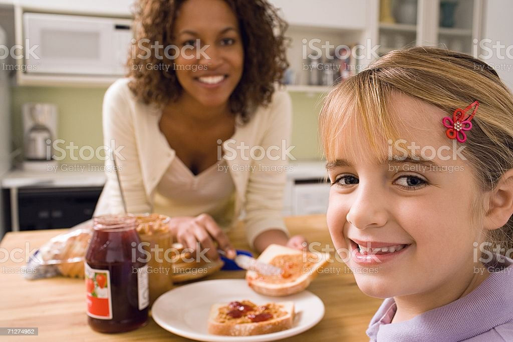 Woman and girl eating in kitchen stock photo