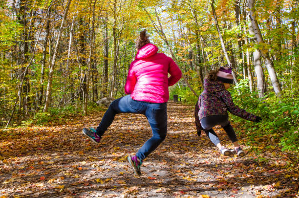 Woman and girl frolicking in a footpath in the woods