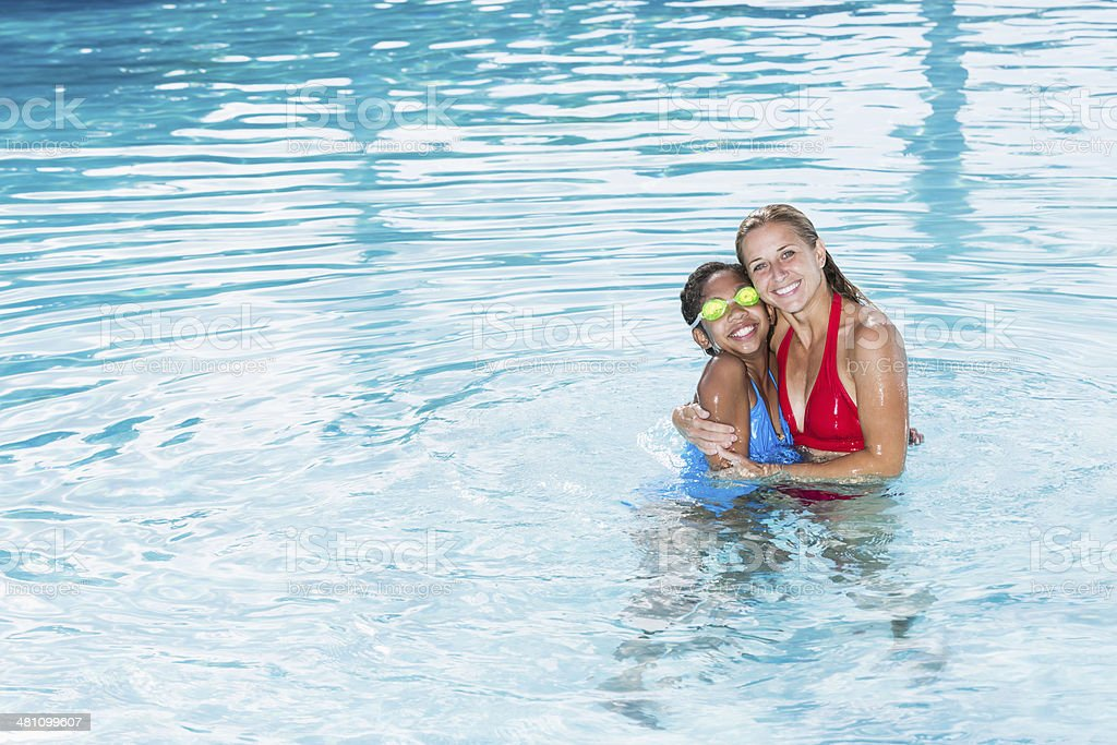 Woman and girl in swimming pool stock photo